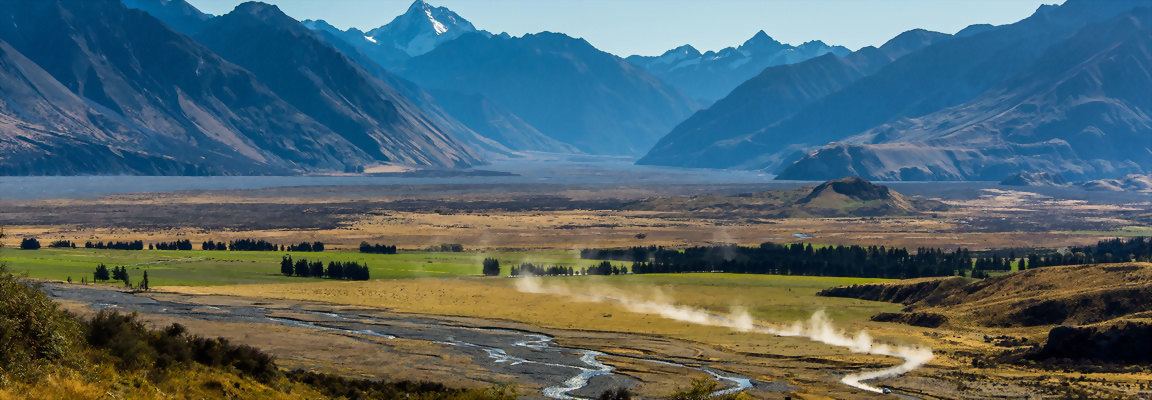 Car travels down gravel road in NZ's Southern Alps