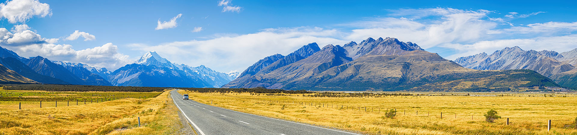 car driving on South Island New Zealand road surrounded by mountains