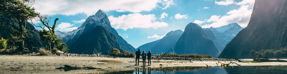 3 visitors enjoying the view of Mitre Peak in Milford Sound