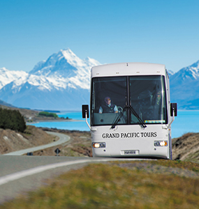 Grand Pacific Coach on road with Mt cook in background