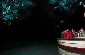 A boat glides under a canopy of glowworms in Waitomo