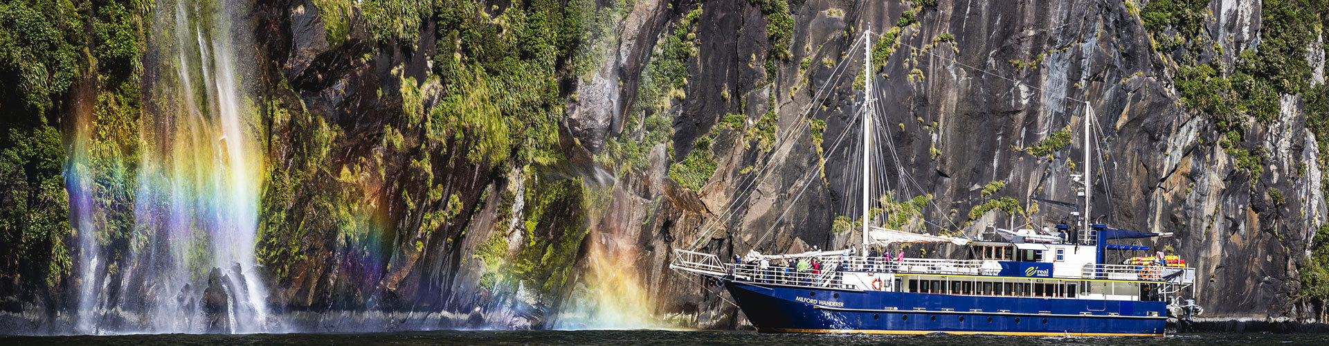 Cruise boat on Milford Sound underneath waterfall
