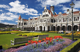 Profile of the Dunedin Railway station with flowers in the front