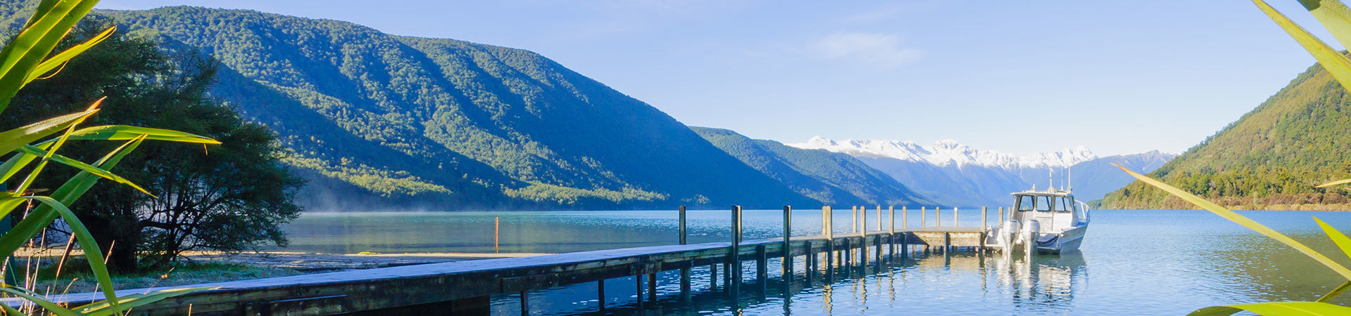 View of wharf and boat surrounded by bush clad hills in Nelson Lakes region, New Zealand
